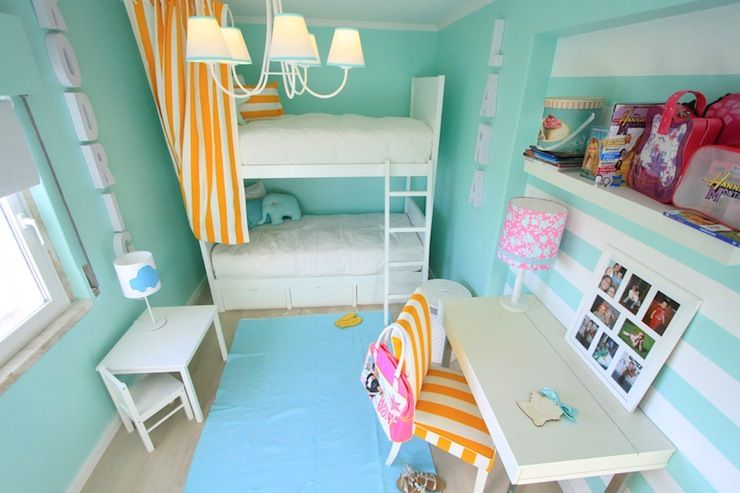 Fun tween girls room with turquoise blue walls paint color  white bunk  beds  white yellow striped curtains pillows  ocean blue rug layered over  beige carpet. Suzie  Ana Antunes   Fun tween girl s room with turquoise blue