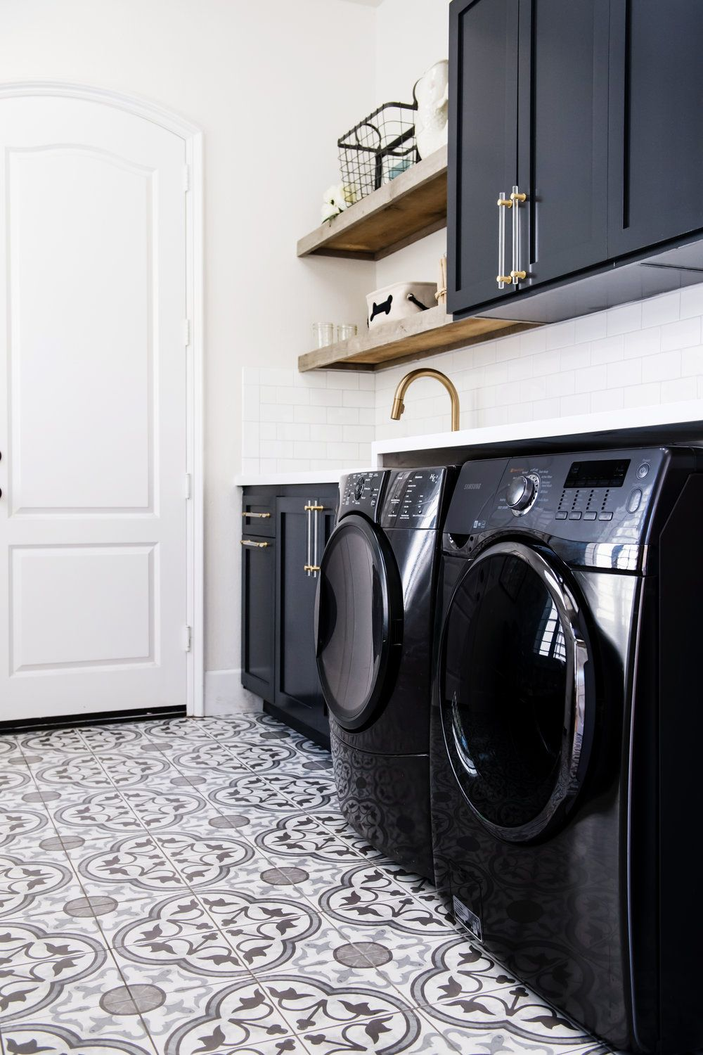 Dark Cabinetry Paired With Black Washer And Dryers In This Playful