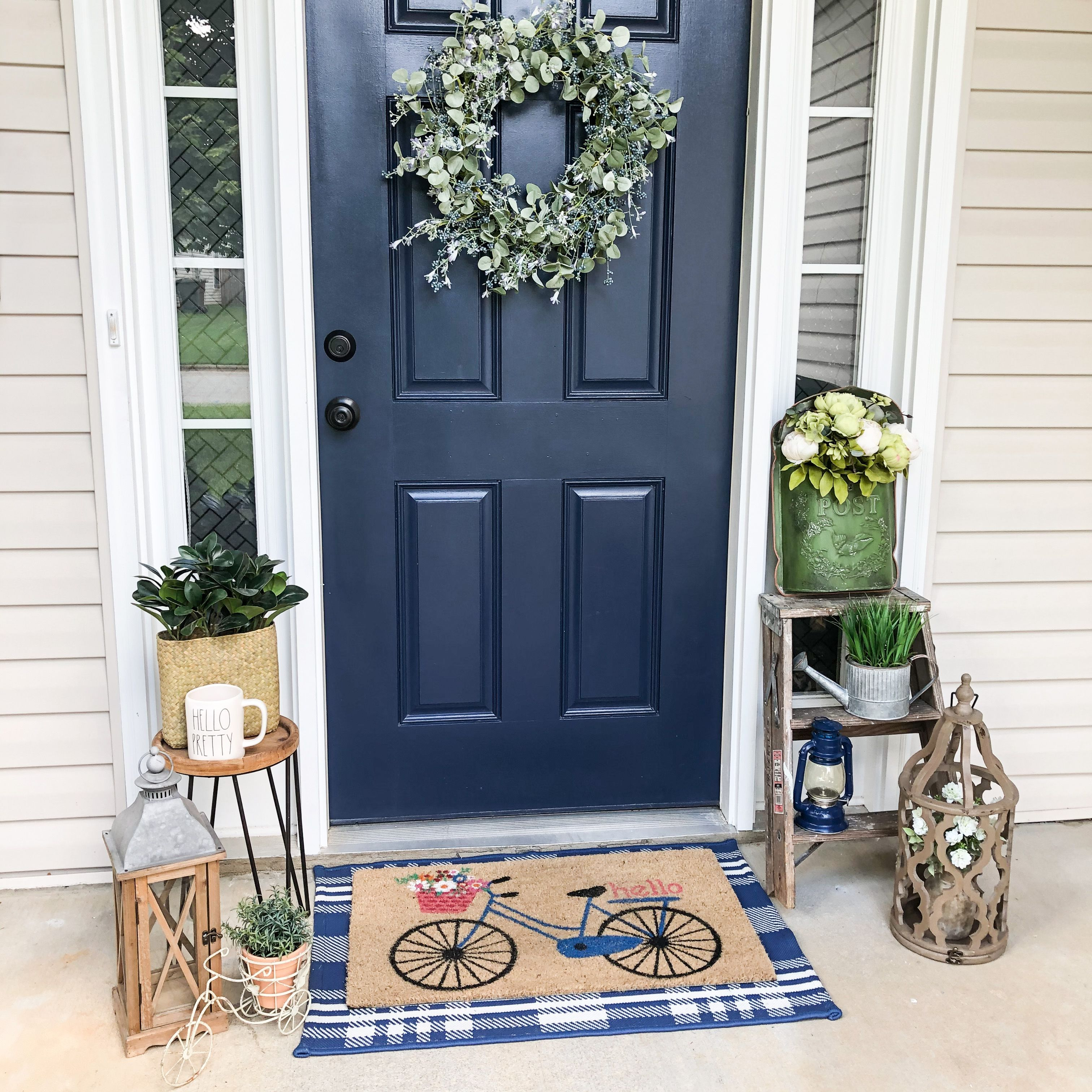 #porchdecor #outdoordecorations #bluefrontdoor #farmhousestyle #layereddoormats #lanternshomedecor #ladderdecor #fauxplants #exteriordecor