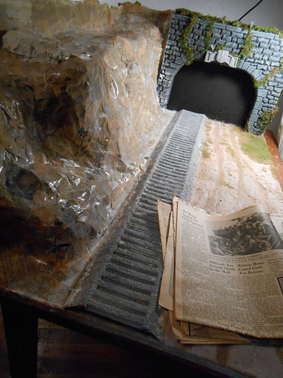 Diorama under construction to showcase a German rail gun.  Mountainside is fashioned from newspapers from 1940-44.
