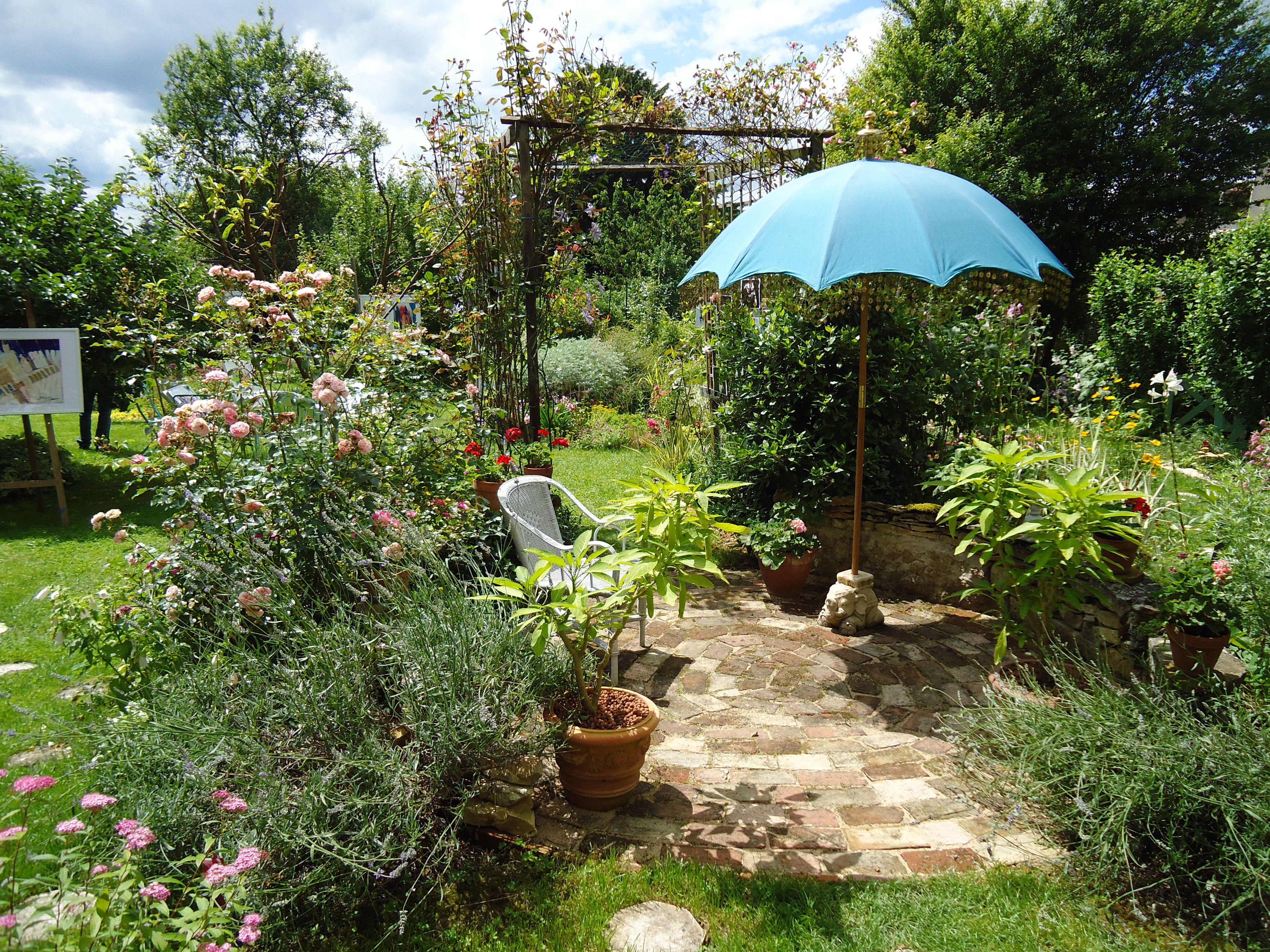 Plantes De Terrasse Arbustes terrasse en briques anciennes, parasol indien dans le jardin