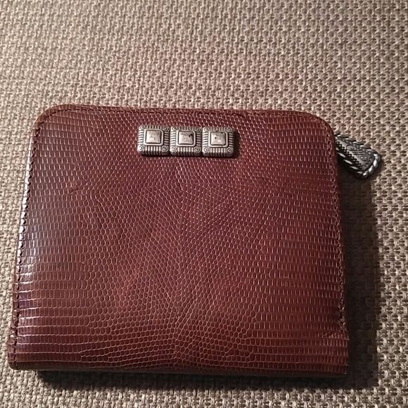 BRIGHTON Brown Wallet Nice !! Great condition !! Silver design on front is a little tarnished, is still pretty. Snap opening. Interior has ID window, slip pocket.other side has slip pocket,photo window. Bill section.Key ring is missing. Top zipper section for change with 2 pickets. Brighton Bags Wallets