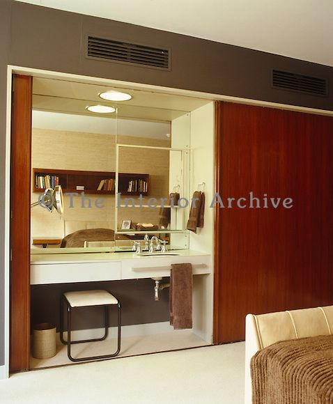 Wardrobe With Table: The Bedroom Features A Built-in Dressing Table And Wash