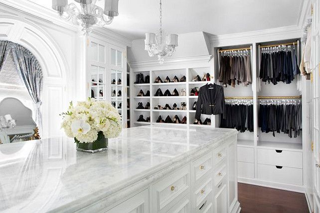 Gorgeous Closet Features Two Chandeliers Illuminating A Long Island Fitted With Drawers For Accessories Topped Marble Countertop