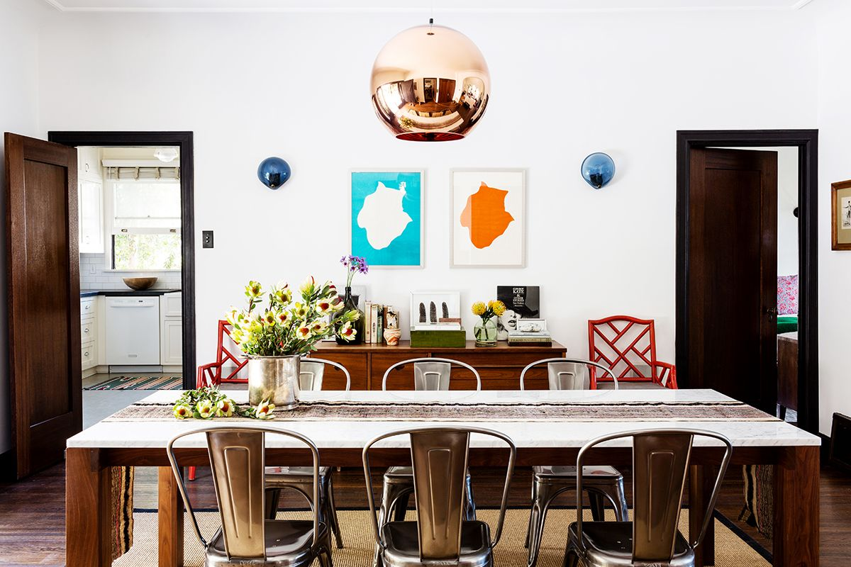 Bright dining space with rose gold bulb chandelier, modern chairs, colorful art, and marble table