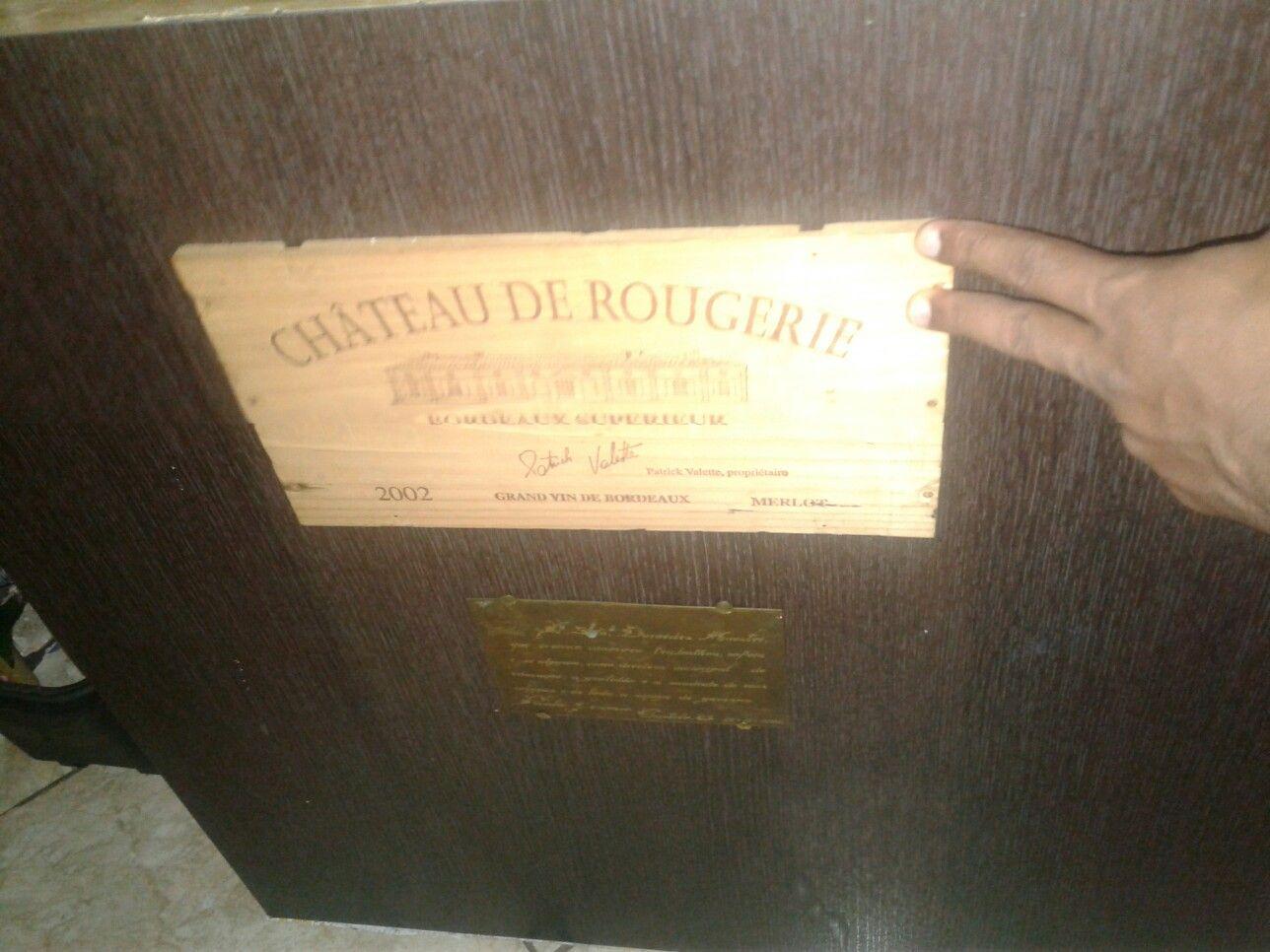 Frente de um caixote de vinho e mais abaixo uma placa de homenagem de um quadro sem uso .usados como com mestria.