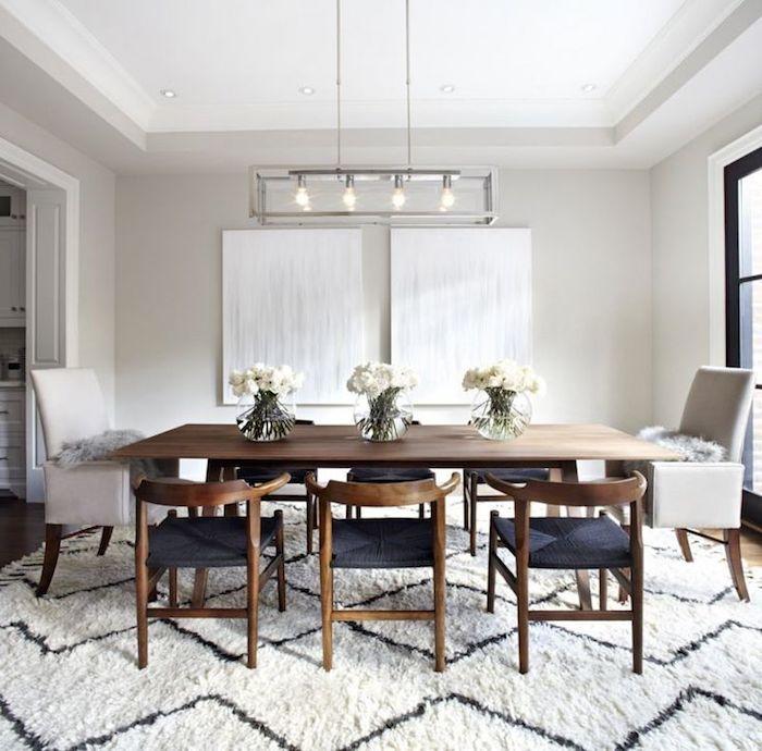 mesa del comedor con alfombra grande, dos cuadros y sillas