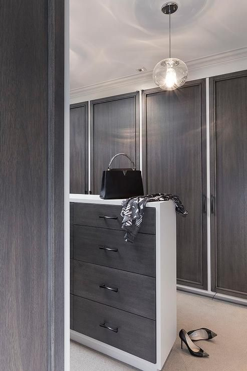 Modern Walk In Closet Features A Slim Two Tone Island Fitted With Dark