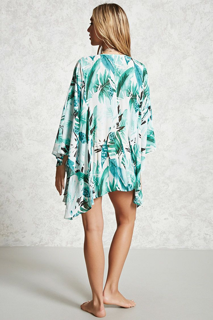 4690096388 A semi-sheer woven swim cover-up kimono featuring an allover tropical  print, open front, long kimono sleeves, side slits, and a handkerchief hem.