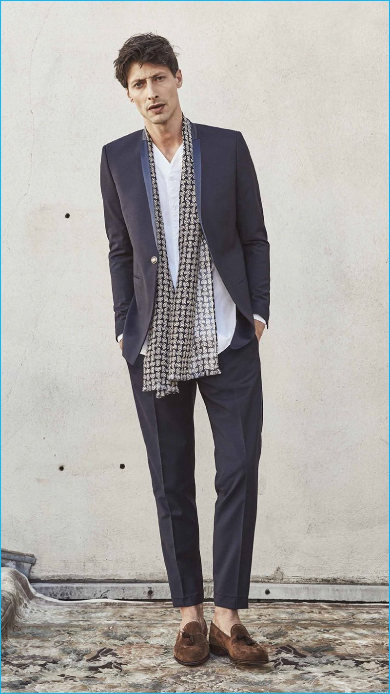 aa12defded Appearing in The Kooples' spring-summer 2017 men's lookbook, Jonas Mason  wears a one-button suit with a collarless shirt and scarf.