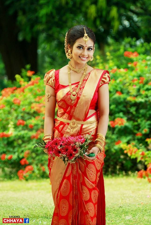 Traditional Southern Indian bride wearing bridal silk saree, jewellery and hairstyle. Temple ...