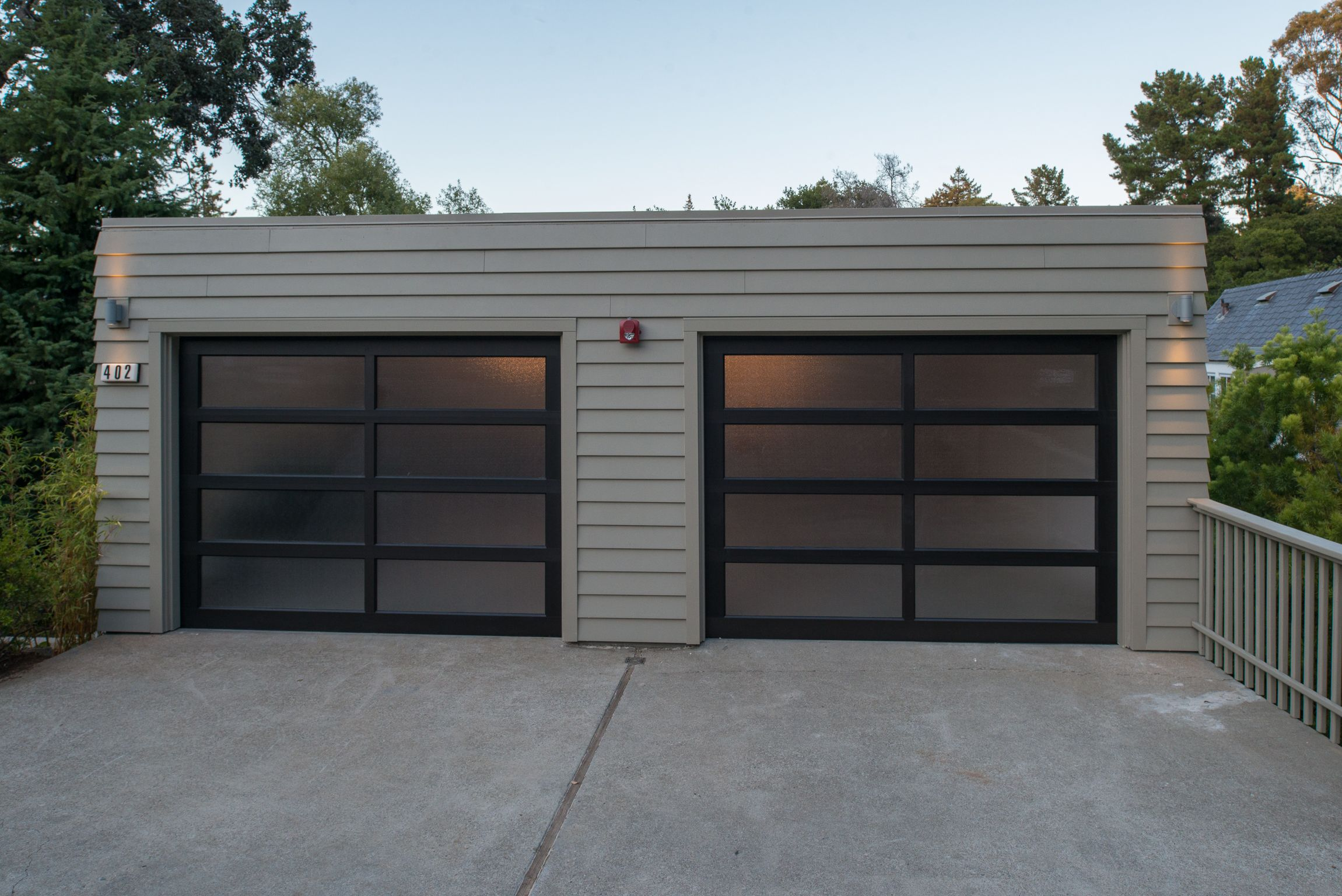 A contemporary garage with beige siding and a black framed for Flat roof garage with deck plans