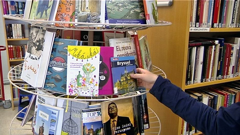 Henkilö ottaa kirjaa kirjaston hyllystä. Number of public libraries in Finland is down by half since 1980s but the number of volumes per library is up substantially.