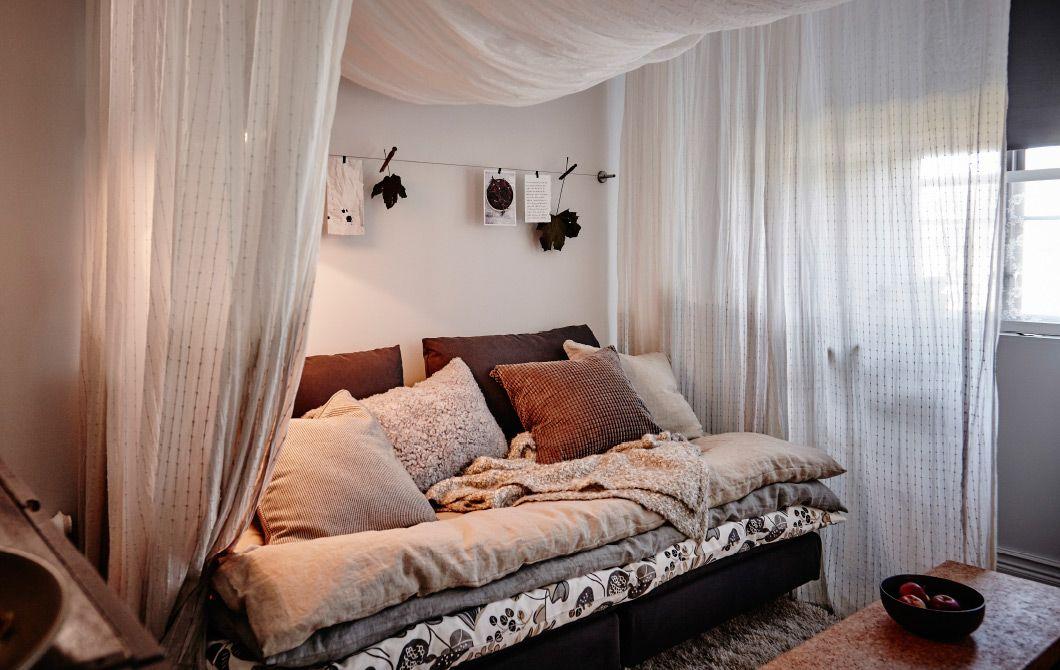 Muhkea sohvasänky täynnä peittoja, tyynyjä ja huopia.