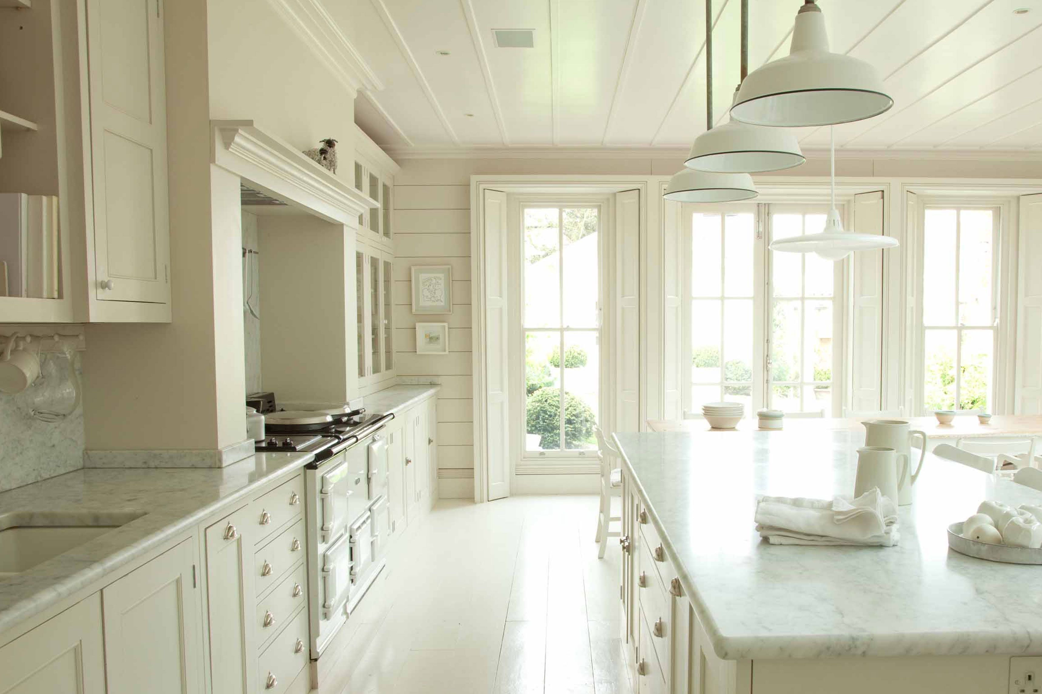 White country kitchen with long dinng table and glass wall cabinets ...