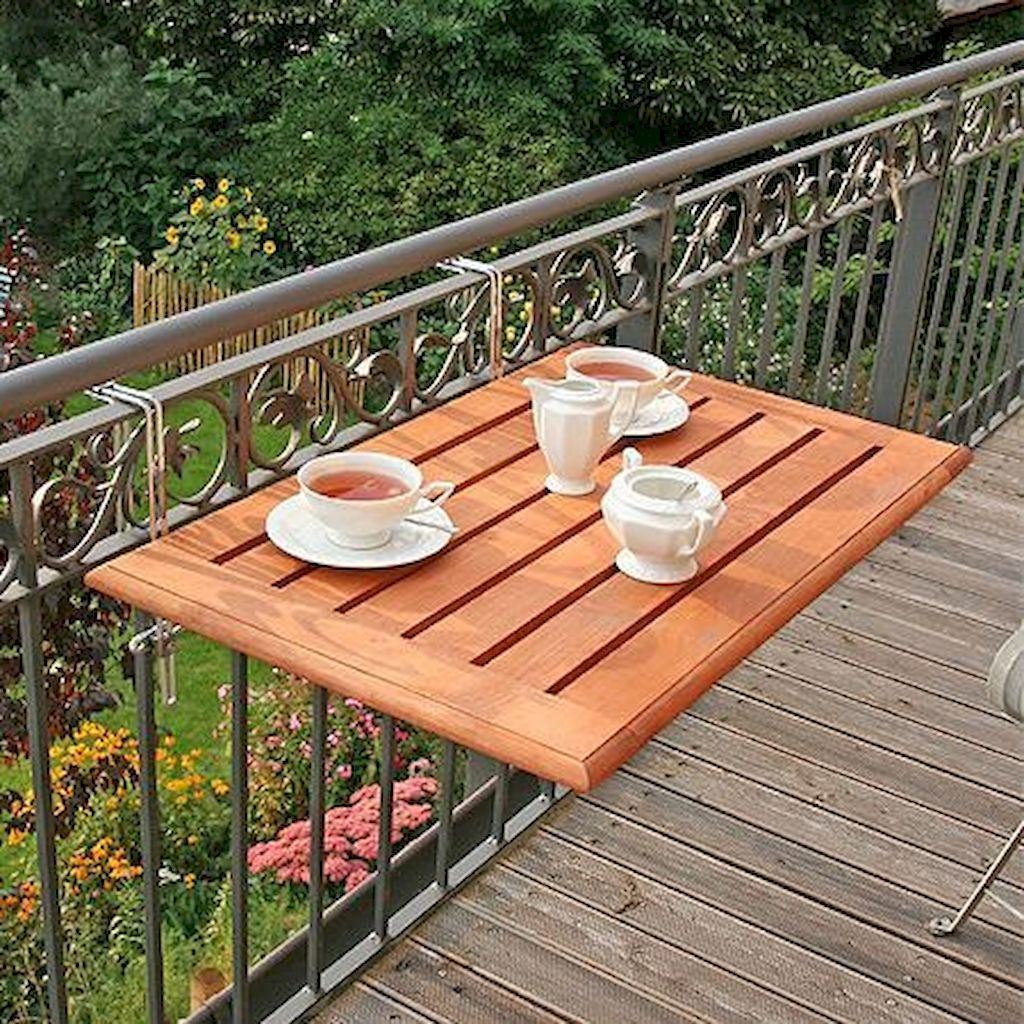 A small balcony furnished with a foldable table and three foldable