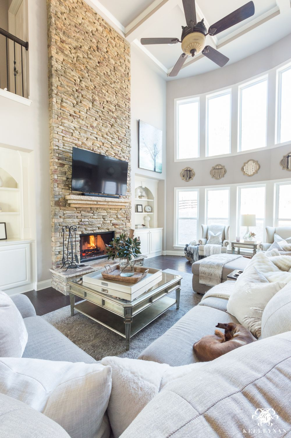 Stacked stone living room fireplace with two story row of windows ...