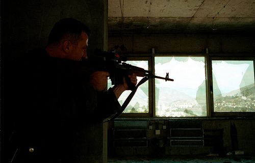 A Bosnian Croat sniper takes careful aim at a group of Bosnian Moslem civilians shopping at an outdoor market in the divided city of Mostar, Bosnia, on Tuesday, August 17, 1993.