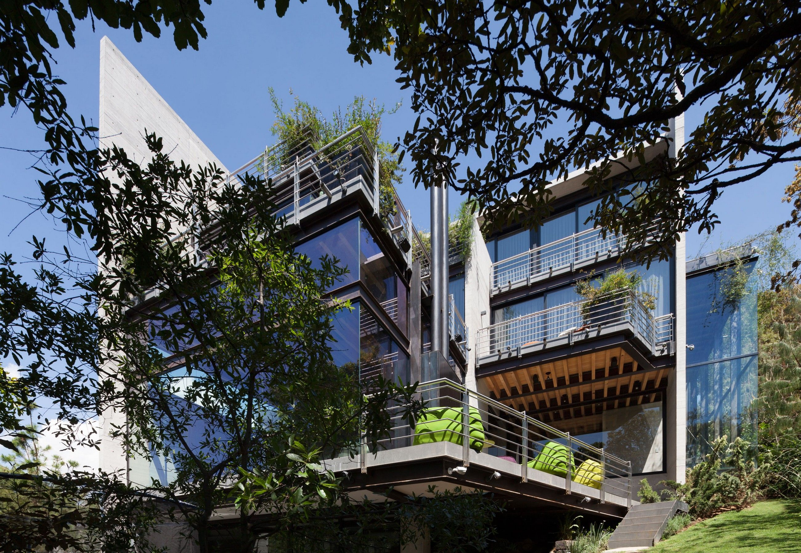 The house consists of two very geometric separate volumes of concrete, one for services and other for the principal areas of the house. The two bodies are joined using steel bridges with glass floor that do not touch the trees and the forest and seems