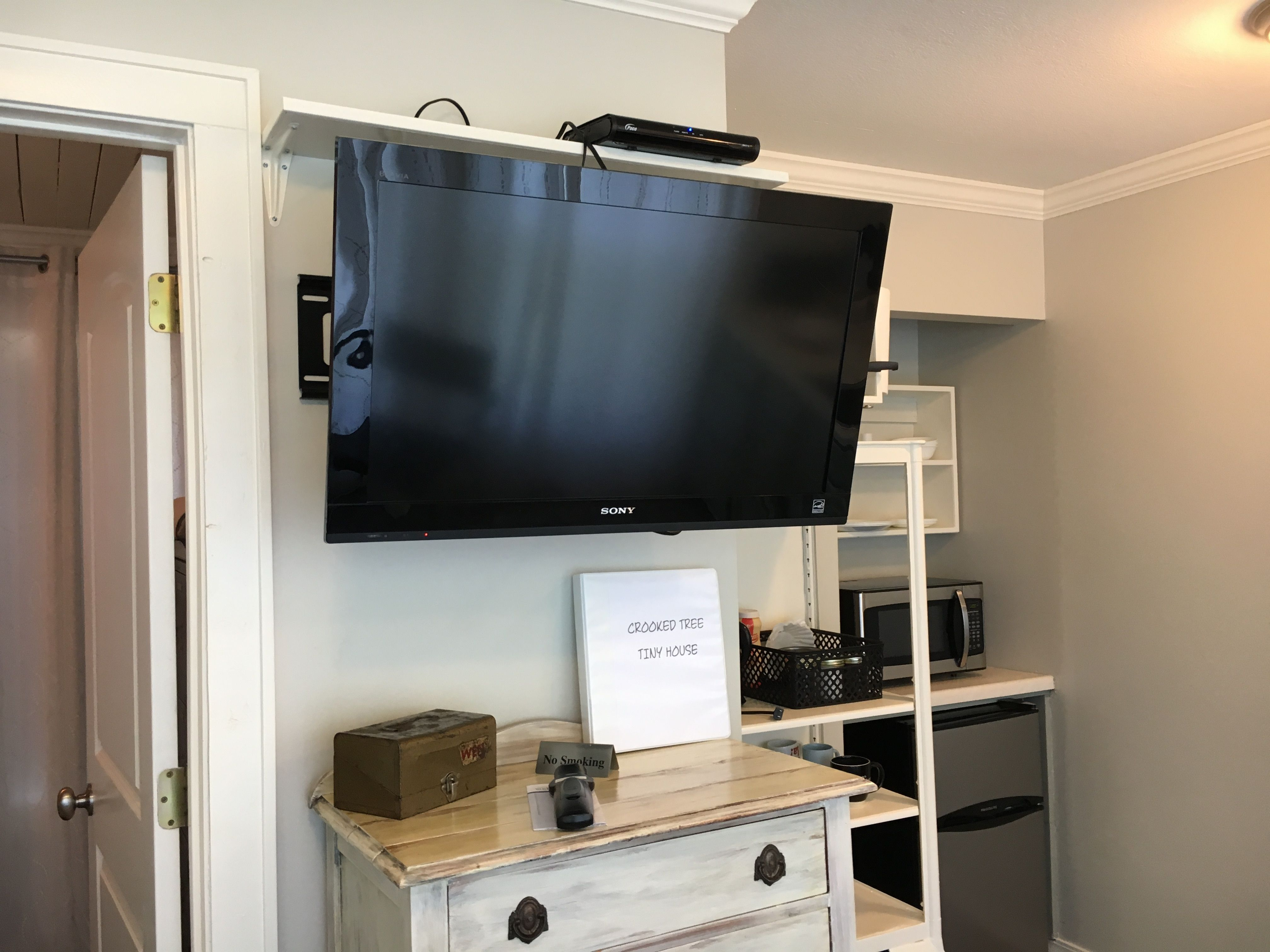 Mounting The Flat Screen Tv On The Wall Allows Us To View It From Different Places In The Living And Kitchen Ar Tiny House Furniture Tiny Houses For Rent House