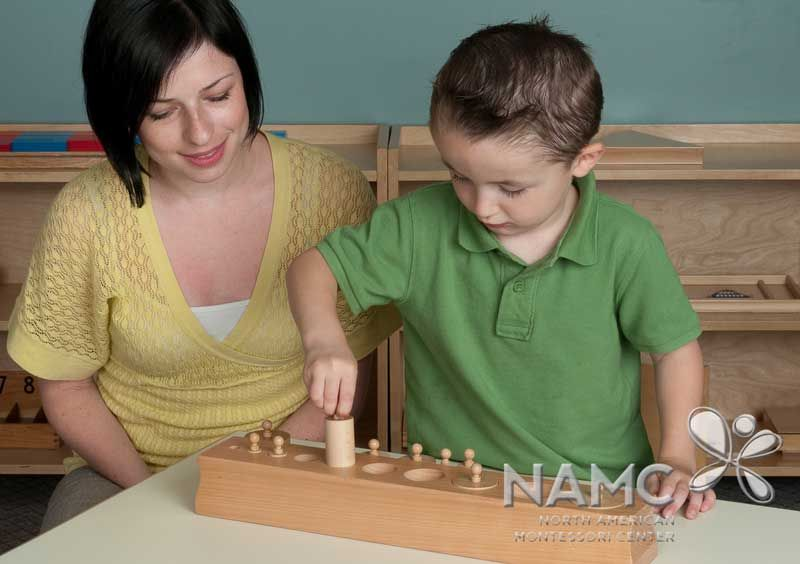 NAMC circle of inclusion montessori materials built in control of error. Boy and teacher with cylinder blocks