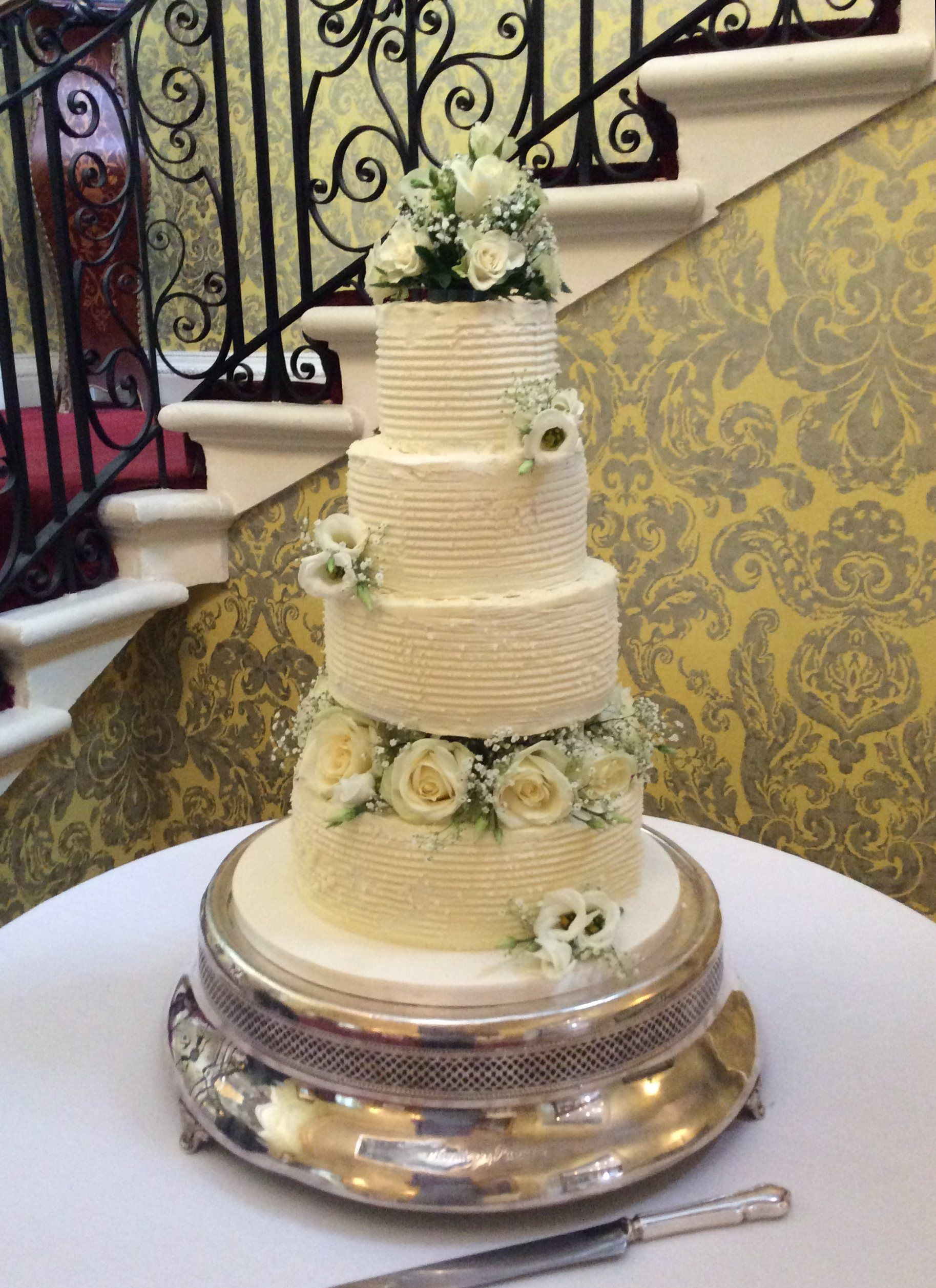4 tier buttercream frosted cake decorated with fresh flowers and ...