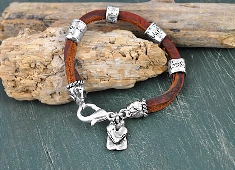 """Two rich brown pieces of leather lace are twisted and bound by beads that read """"to conquer fear is the beginning of wisdom"""". This unique bracelet has heart carved end caps and a heart dangling beside a lobster clasp. 7 1/2"""" length"""