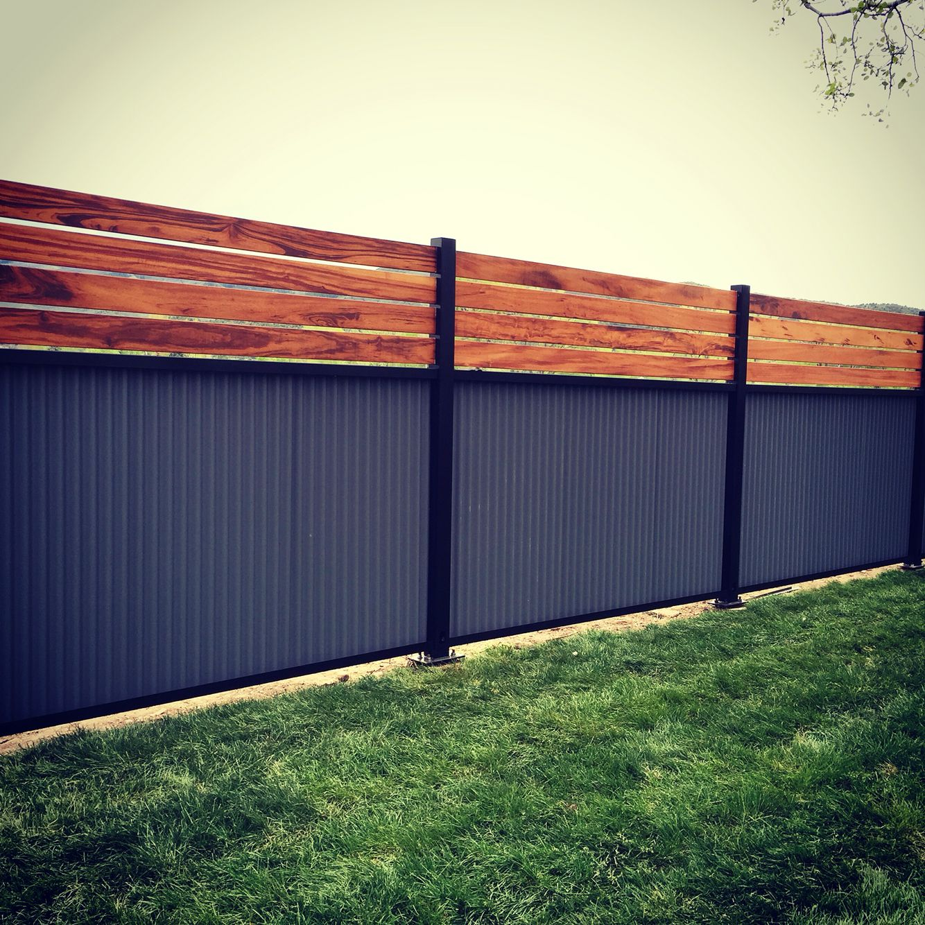 Custom privacy fence built out of metal post tiger wood for Wood screen fence