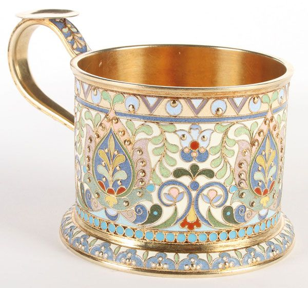 A VERY FINE SILVER GILT AND ENAMELED TEA GLASS HOLDER, OVCHINNIKOV, MOSCOW, 1908-1917. The heavy gilded silver body with slightly flared foot, the sides profusely enameled in scrolling foliage and flower forms and the upper border with geometric designs and silver beading throughout.