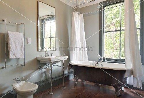 Freistehende Vintage Badewanne Mit Duschvorhang Vor Fenster, Daneben  Waschbecken Auf Metallgestell Unter Wandspiegel Im Bad