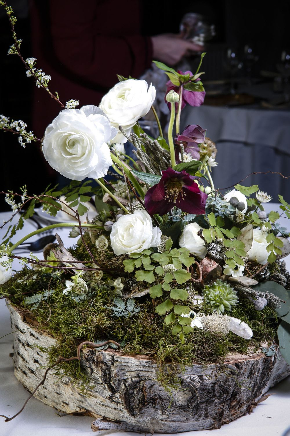 Woodland centre piece! Tree slice base with a bed of moss, ranunculus & hellebores. Winter | Spring natural, rustic wedding Flowers | Katie Laura Flowers | Paul Maven Photography