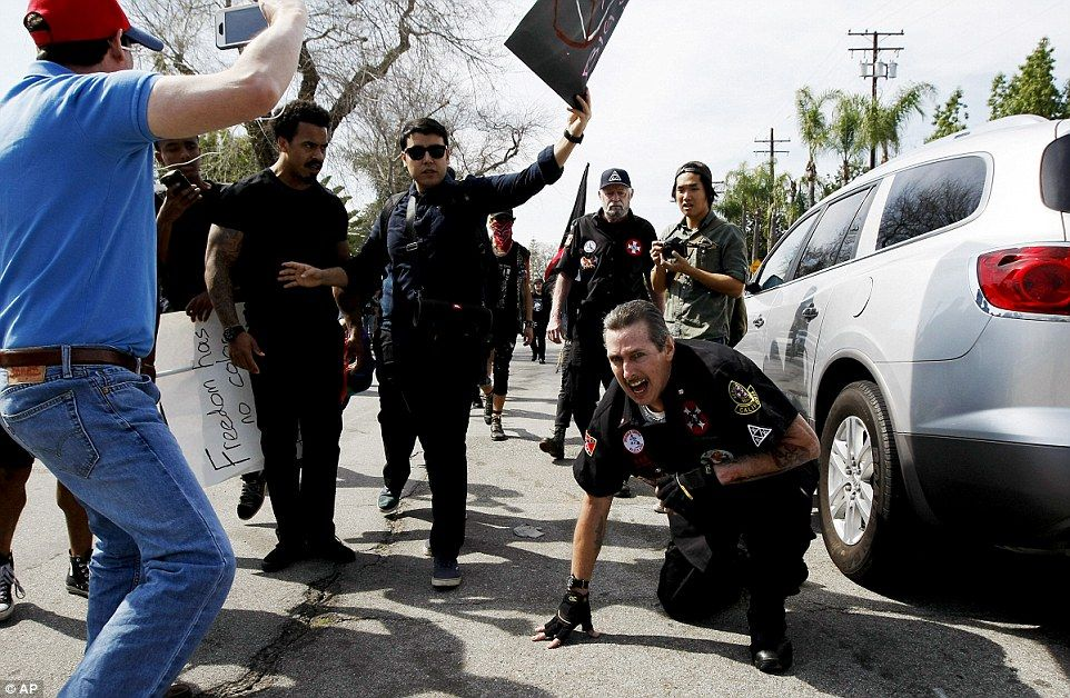 Counter protesters are shown above as they taunt an injured Klansman. The event quickly escalated into violence and four people were arrested following the melee