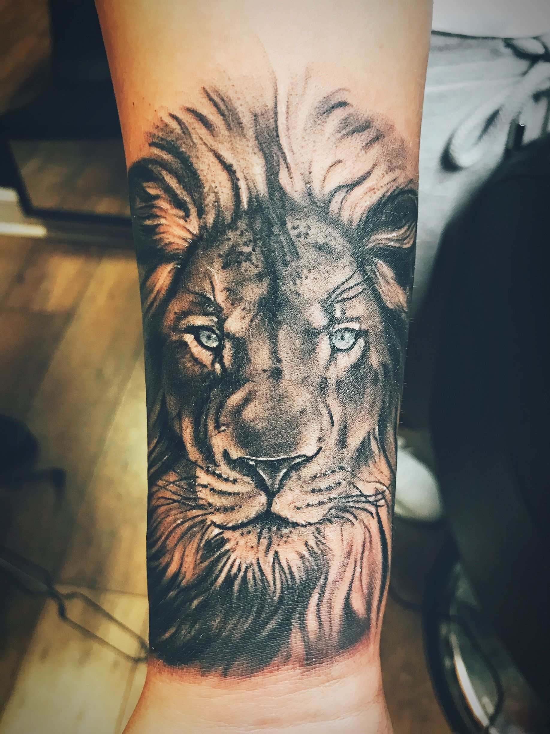 Black and white Lion wrist tattoo with blue eyes Lion