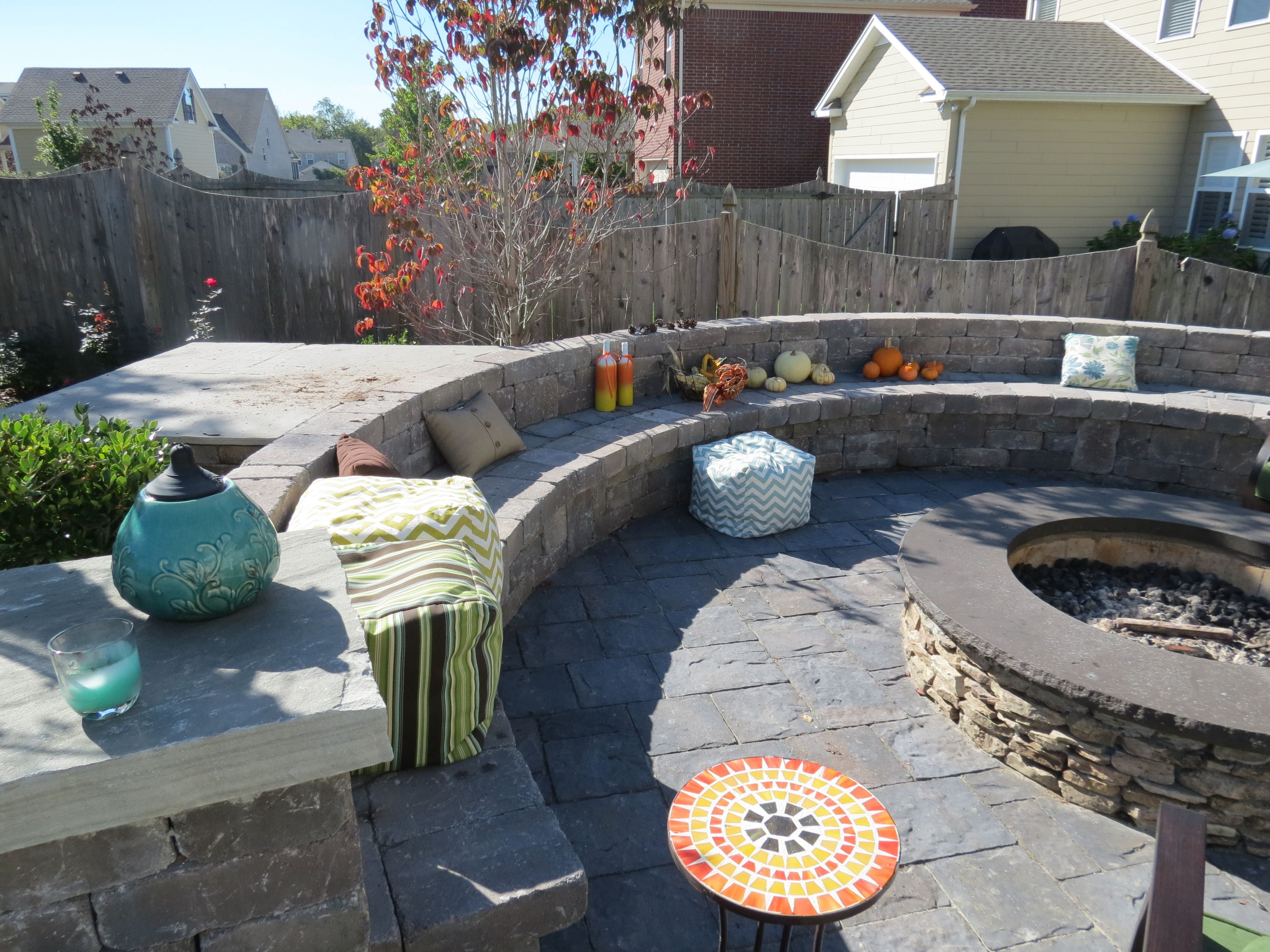 Backyard brick paver patio with natural stone fire pit and seat