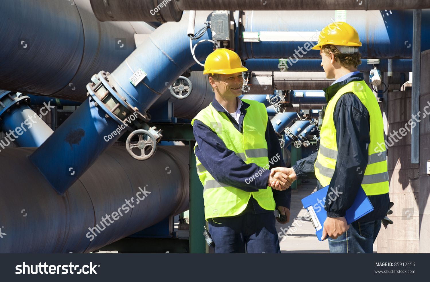 Two engineers meeting outside at the piping of an