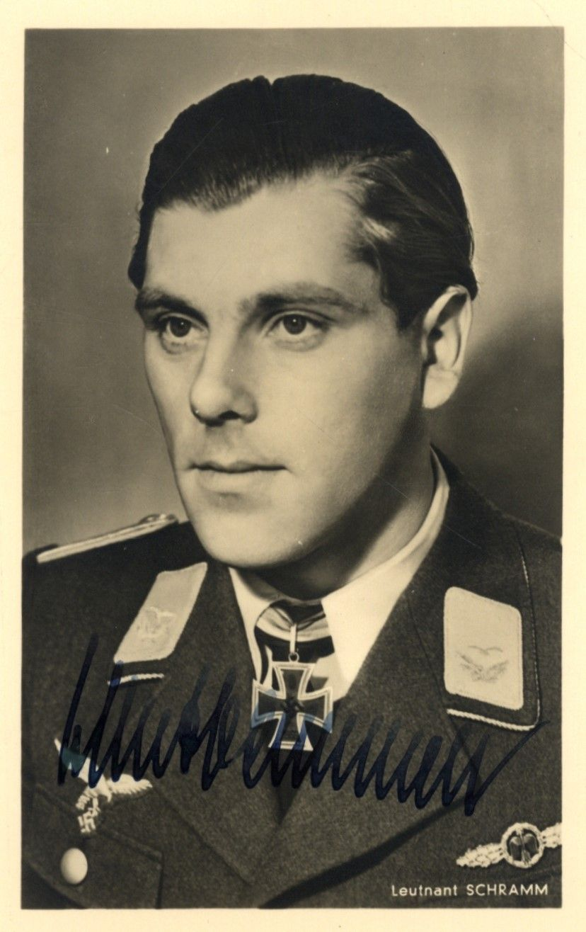 SCHRAMM HERBERT: (1913-1943) German Luftwaffe Ace of World War II, Knight's Cross winner with Oak Leaves. Vintage signed sepia postcard photograph of Schramm in a head and shoulders pose wearing his uniform and Knight's Cross. Photograph by Heinrich Hoffmann of Munich. Signed in bold dark fountain pen ink with his name alone to a light area at the base of the image. Autographs of Schramm are rare in any form as a result of his early death at the age of 30.