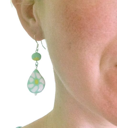 """This whimsical dangle is part of our new Mila Series.  These earrings are hand-sculpted from polymer clay and set on hypo-allergenic stainless steel fishhooks.  This medium length dangle earring measures in at 2 1/4"""" long, by 5/8"""" wide. Focal bead the Mila series white daisy on a minty green background. Shaped polymer clay beads are nestled between clear glass seed beads and threaded on hypo-allergenic stainless steel fish hooks. Colors are white, mint, and yellow."""