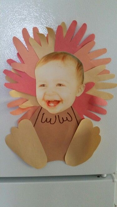 Construction paper turkey with your child's face. I made this by tracing his hands for the feathers and by cutting his picture out of a 4×6 photo. Great as a center piece at thanksgiving! #fallcraftsfortoddlers