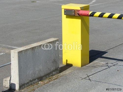 Gelbe Schranke mit schwarzen Streifen und Barriere aus Beton an einem Parkplatz in Bielefeld