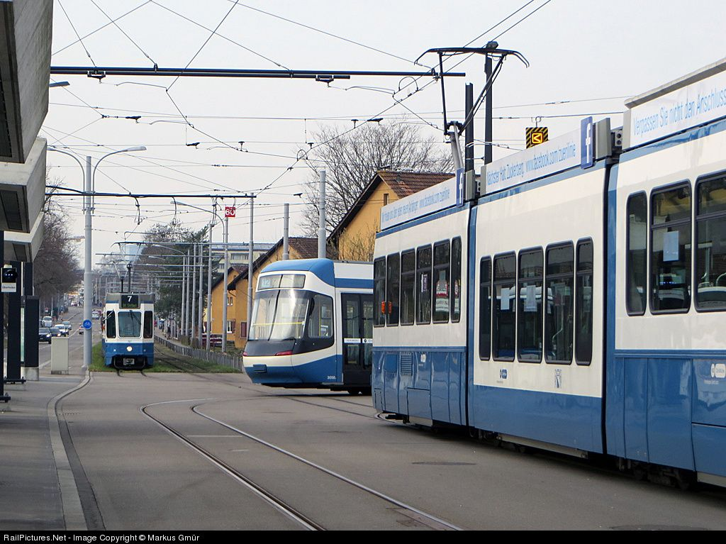 Rush hour in Stettbach; the tramway line #7 (left) waits for to run in the station, the right one (also line #7) waits for departure. The tramway in the middle (line #12) arrives at the station.