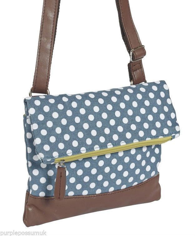 A small medium sized blue and white polka dot print crossbody ...