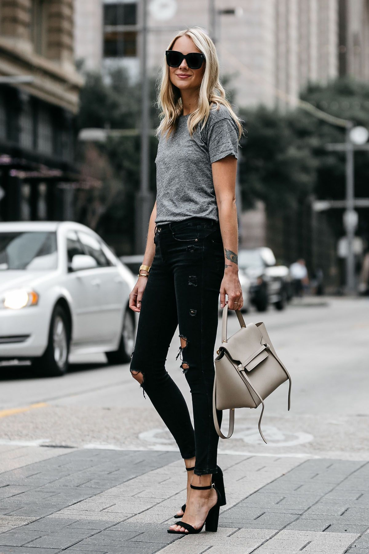 e3b18650849 Blonde woman wearing Madewell grey tshirt zara black ripped skinny jeans  outfit steve madden black ankle strap heels celine belt bag street style  dallas ...