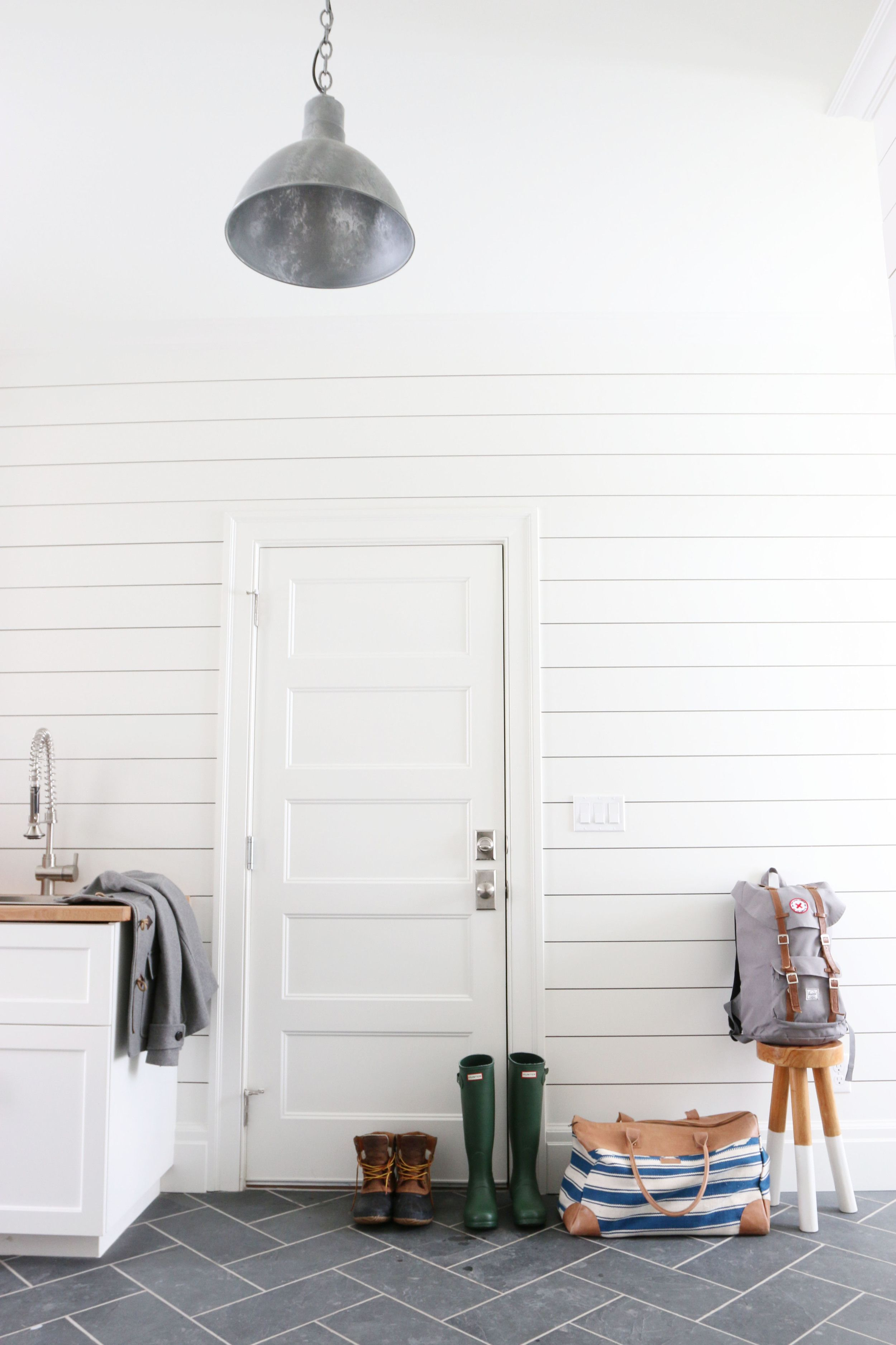mudroom with shiplap and slate herringbone floors