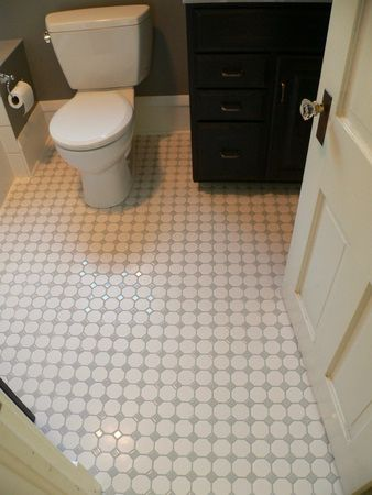 Two inch white hex tiles with gray diamond insets shine on the floor of  this Champaign bathroom remodel. Two inch white hex tiles with gray diamond insets shine on the