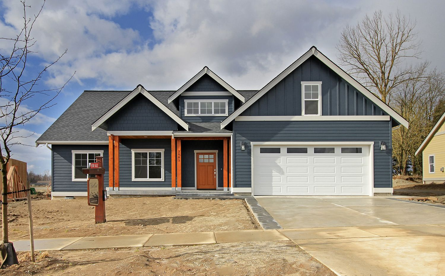 Blue siding craftsman style home with wood posts and front for Craftsman style siding