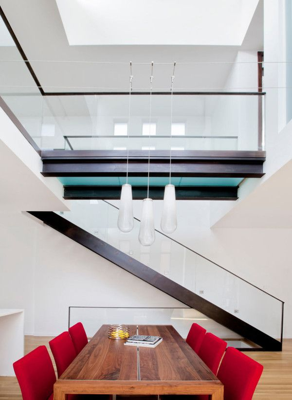 A dining table sits beneath a double-height, light-filled ceiling, with pendant lights suspended from wires.