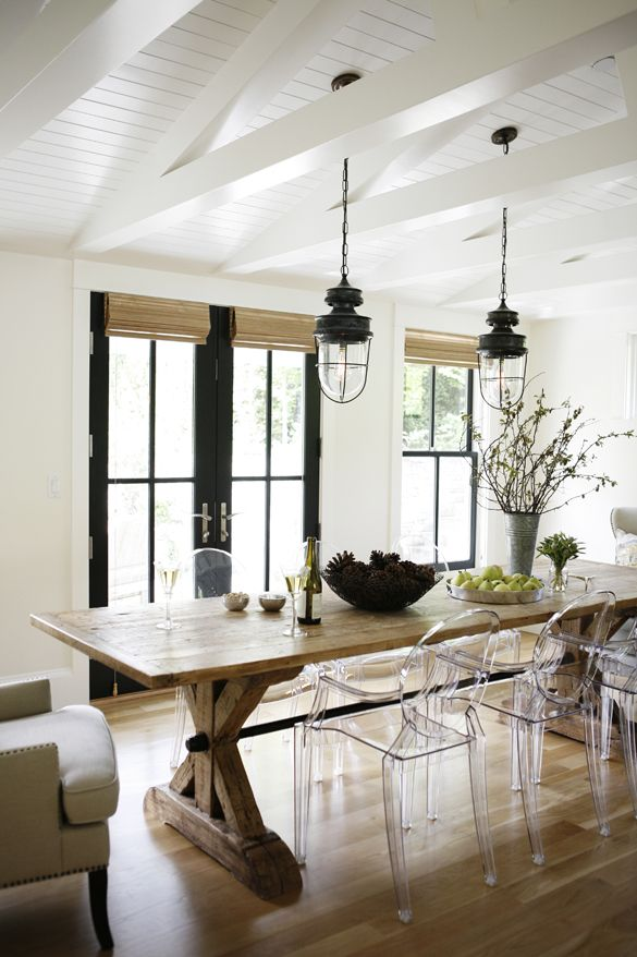 Modern Farmhouse Kitchen Dining Area Lucite Side Chairs Wingback At Head Of Table And Industrial Lighting Beams Roman Shades On French Doors