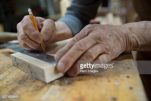 Stock Photo : Close up carpenter measuring and marking wood piece