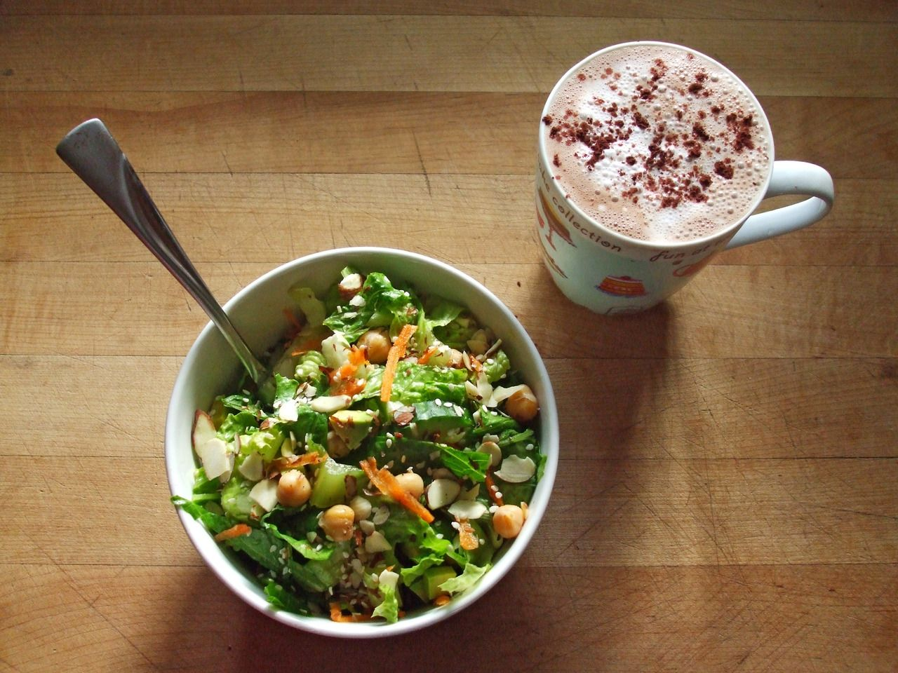 green salad with romaine, cucumber, carrot, avocado, chickpeas, sesame seeds, almonds, and oil & vinegar dressing, and a coconut mocha