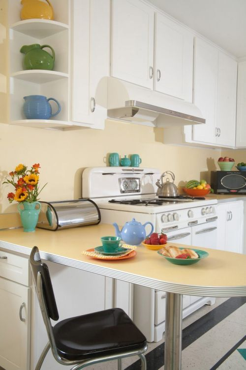 """Margie Grace's new 1940s-style kitchen features a VCT tile """"rug"""" she installed herself, white cabinets and buttercream countertops -- what a perfect space!"""